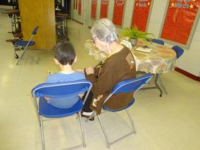 First grade student reads his book to Ginger Malmstrom.